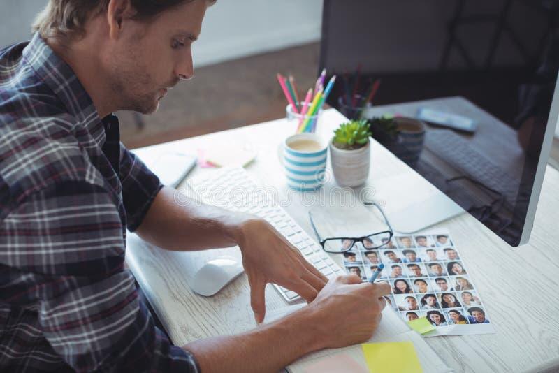 Σοβαρός επιχειρηματίας που γράφει στο βιβλίο στο δημιουργικό γραφείο γραφείων στοκ φωτογραφίες