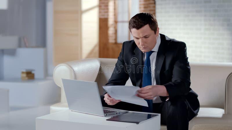 Σοβαρός επιχειρηματίας που ελέγχει την έκθεση επιχείρησης, που λειτουργεί στο lap-top στο σύγχρονο γραφείο στοκ φωτογραφία με δικαίωμα ελεύθερης χρήσης