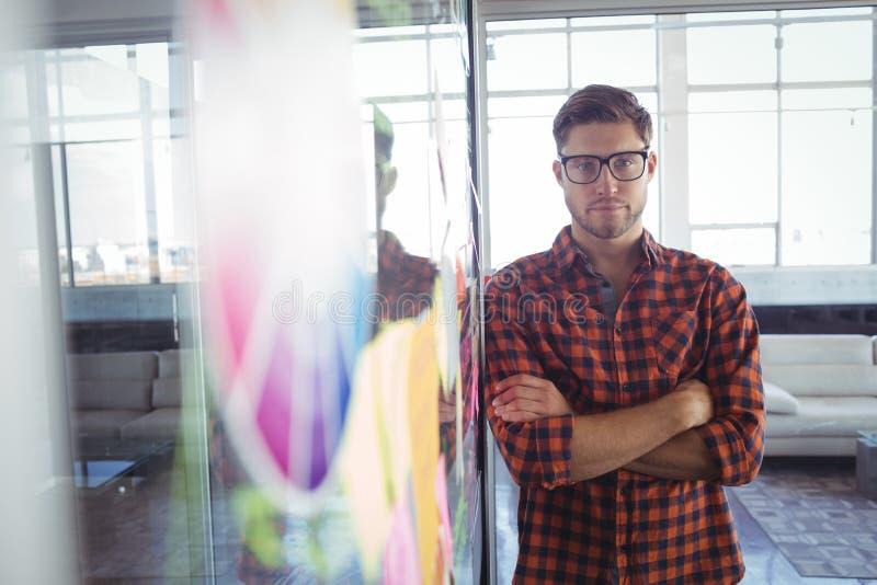 Σοβαρός επιχειρηματίας που υπερασπίζεται τις συγκολλητικές σημειώσεις στο δημιουργικό γραφείο στοκ φωτογραφία με δικαίωμα ελεύθερης χρήσης