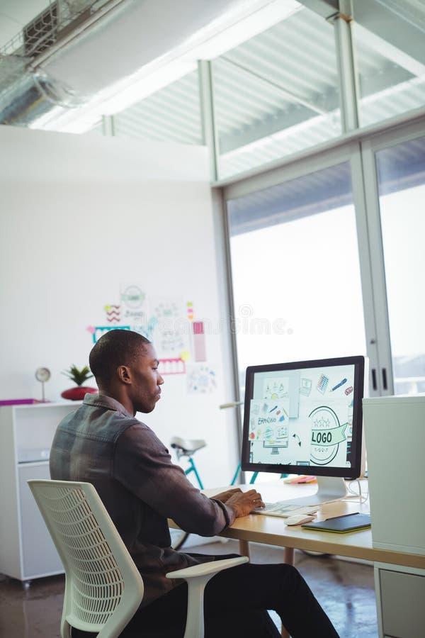 Σοβαρός επιχειρηματίας που χρησιμοποιεί τον υπολογιστή στο δημιουργικό γραφείο στοκ εικόνες