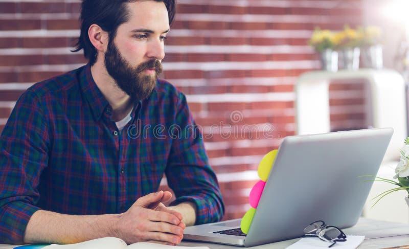 Σοβαρός δημιουργικός συντάκτης που εργάζεται στο lap-top στοκ εικόνες