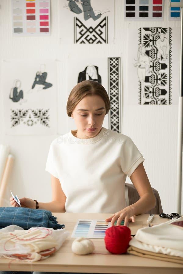 Σοβαρός θηλυκός σχεδιαστής μόδας που επιλέγει swatch χρώματος για νέο ομο στοκ φωτογραφία