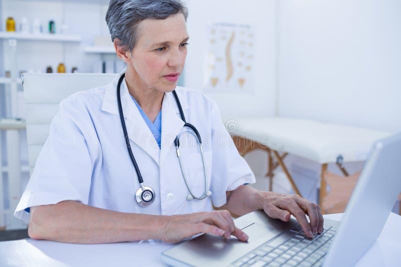 Σοβαρός θηλυκός γιατρός που χρησιμοποιεί το φορητό προσωπικό υπολογιστή της στοκ φωτογραφία