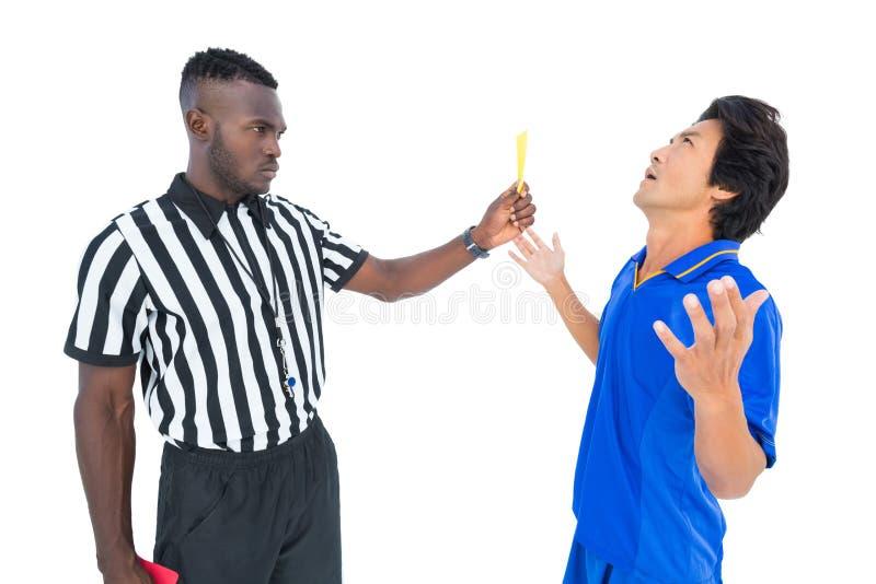 Σοβαρός διαιτητής που παρουσιάζει κίτρινη κάρτα στο φορέα στοκ φωτογραφία