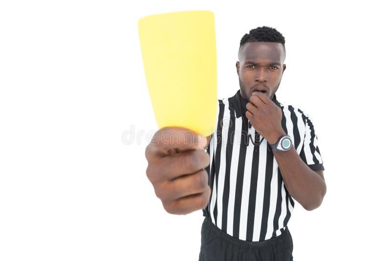 Σοβαρός διαιτητής που παρουσιάζει κίτρινη κάρτα στοκ εικόνα
