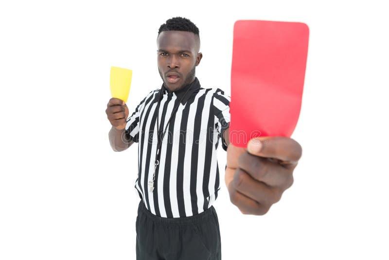 Σοβαρός διαιτητής που παρουσιάζει κίτρινη και κόκκινη κάρτα στοκ εικόνες