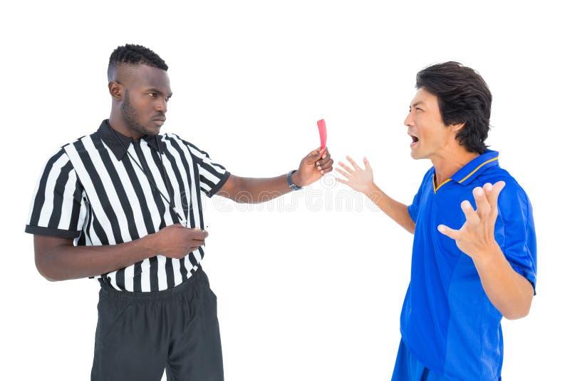 Σοβαρός διαιτητής που παρουσιάζει κόκκινη κάρτα στο φορέα στοκ εικόνες