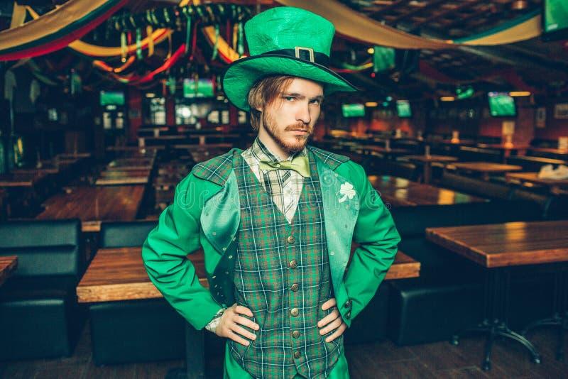 Σοβαρός και συγκεντρωμένος νεαρός άνδρας στην πράσινη στάση κοστουμιών μόνο στο μπαρ Κρατά τα χέρια στα ισχία και κοιτάζει στη κά στοκ φωτογραφίες