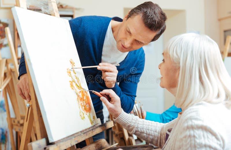 Σοβαρός καλλιτέχνης που βοηθά την ηλικιωμένη γυναίκα στη ζωγραφική του σχολείου στοκ φωτογραφίες με δικαίωμα ελεύθερης χρήσης