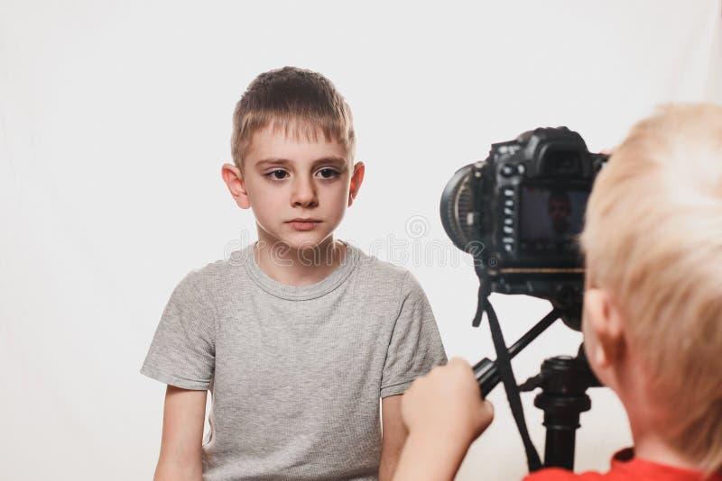 Σοβαρός μαθητής που δίνει συνέντευξη, το αγόρι με την βιντεοκάμερα Νέος blogger με βίντεο Λευκό φόντο στοκ φωτογραφία με δικαίωμα ελεύθερης χρήσης