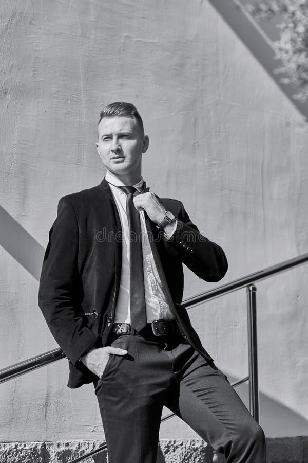 Σοβαρός νέος επιχειρηματίας που φορά την μπλούζα και το μαύρο παντελόνι με τα μπλε μάτια στοκ εικόνα με δικαίωμα ελεύθερης χρήσης