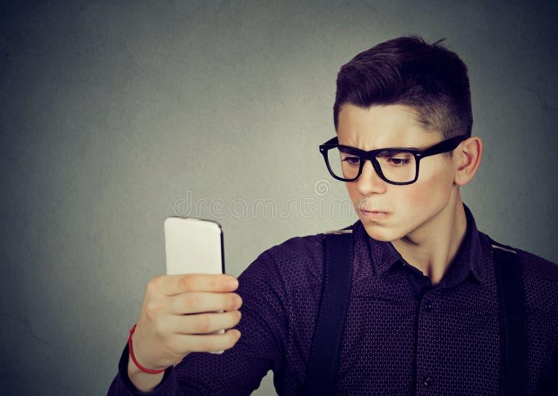 Σοβαρός νεαρός άνδρας που παίρνει ένα selfie στοκ εικόνα