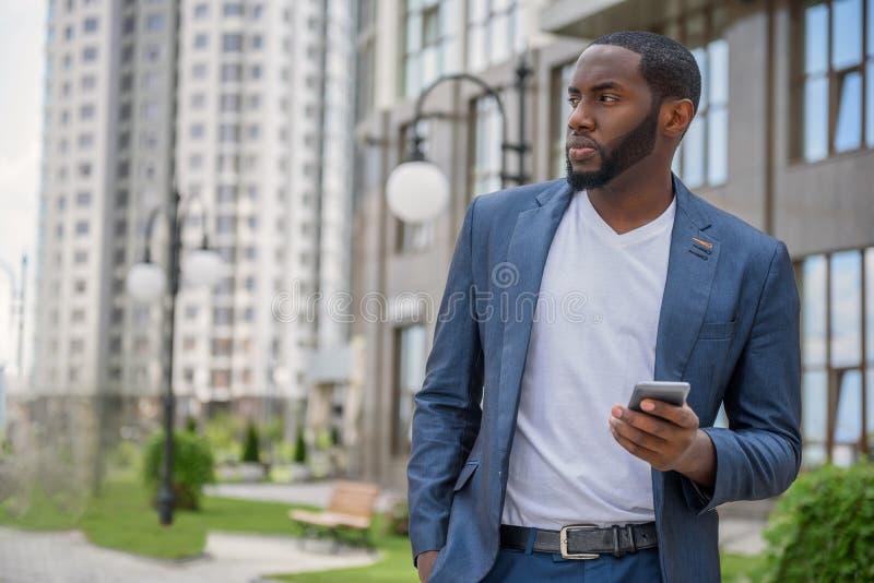 Σοβαρός νεαρός άνδρας που χρησιμοποιεί το κινητό τηλέφωνο υπαίθρια στοκ εικόνες με δικαίωμα ελεύθερης χρήσης