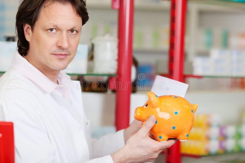Σοβαρός φαρμακοποιός με τη piggy τράπεζα στοκ εικόνες με δικαίωμα ελεύθερης χρήσης