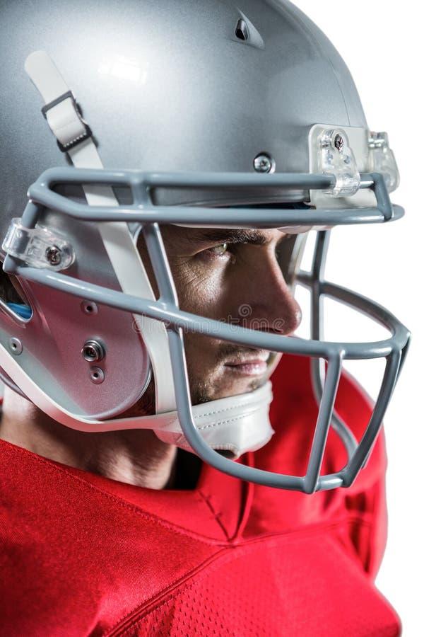 Σοβαρός φορέας αμερικανικού ποδοσφαίρου στο κόκκινο Τζέρσεϋ που κοιτάζει μακριά στοκ εικόνες