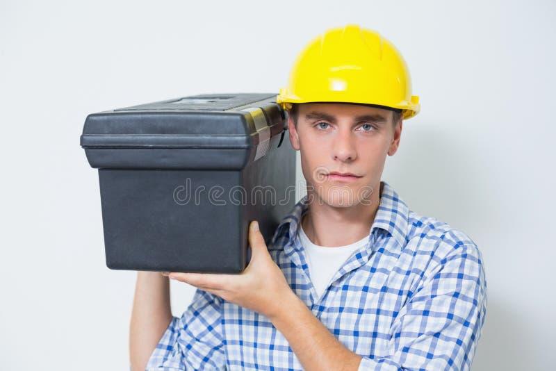 Σοβαρός handyman στην κίτρινη σκληρή φέρνοντας εργαλειοθήκη καπέλων στοκ φωτογραφίες με δικαίωμα ελεύθερης χρήσης