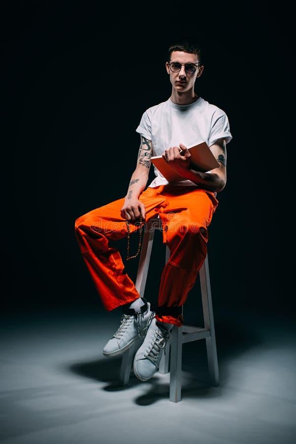 Σοβαρό άτομο πορτοκαλή σε ομοιόμορφο με τις μανσέτες στα πόδια που διαβάζουν τη Βίβλο και που κάθονται στο σκαμνί στοκ φωτογραφίες με δικαίωμα ελεύθερης χρήσης