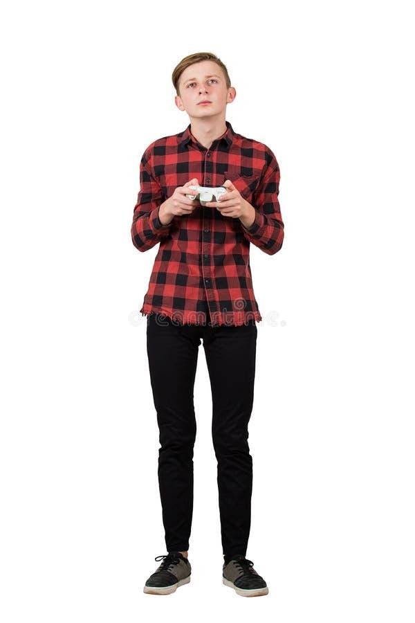 Σοβαρό έφηβο αγόρι που παίζει βιντεοπαιχνίδια απομονωμένο με λευκό φόντο Ένας τύπος με πρόθεση, στέκεται στα αυτιά κρατώντας ένα  στοκ φωτογραφία