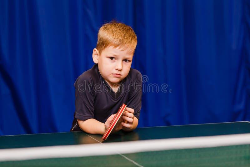 Σοβαρό αγόρι στην γκρίζα μπλούζα και ρακέτα υπό εξέταση στο μπλε υπόβαθρο στοκ φωτογραφίες