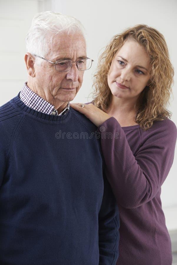 Σοβαρό ανώτερο άτομο με την ενήλικη κόρη στο σπίτι στοκ εικόνα με δικαίωμα ελεύθερης χρήσης