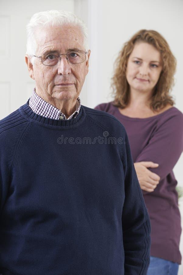 Σοβαρό ανώτερο άτομο με την ενήλικη κόρη στο σπίτι στοκ εικόνα