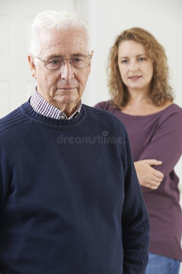 Σοβαρό ανώτερο άτομο με την ενήλικη κόρη στο σπίτι στοκ εικόνες