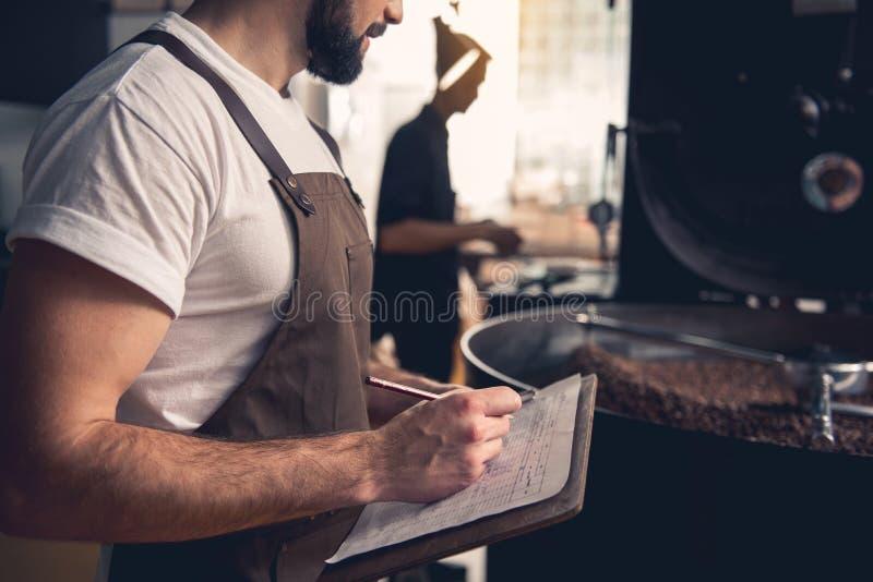 Σοβαρό αρσενικό που σημειώνει για την προετοιμασία των σιταριών καφέ στοκ εικόνα με δικαίωμα ελεύθερης χρήσης