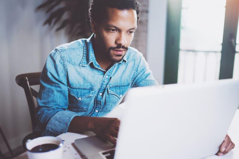 Σοβαρό γενειοφόρο αφρικανικό άτομο που εργάζεται στο lap-top ξοδεύοντας το χρόνο στο σπίτι Έννοια της νέας χρησιμοποίησης επιχειρ στοκ εικόνα με δικαίωμα ελεύθερης χρήσης