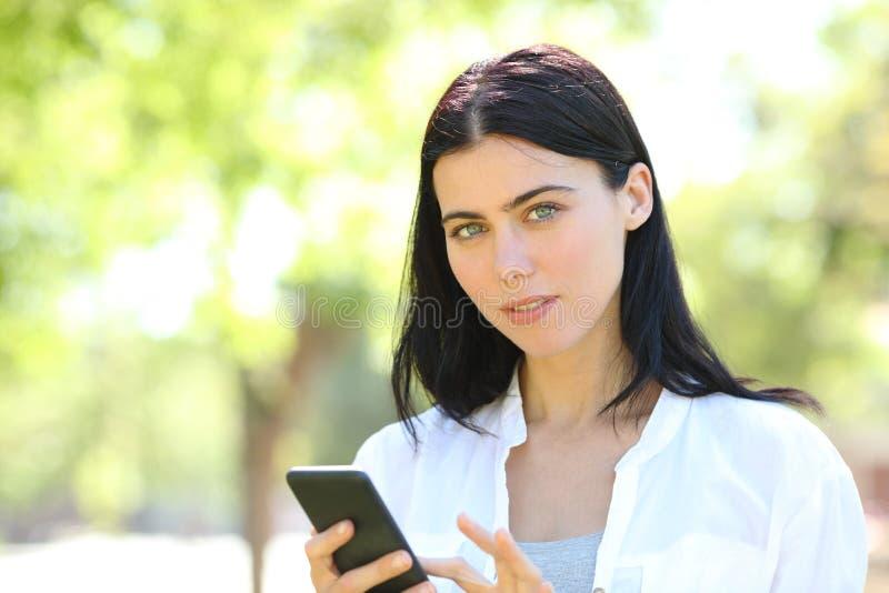 Σοβαρό ενήλικο τηλέφωνο εκμετάλλευσης γυναικών που εξετάζει τη κάμερα στοκ φωτογραφία με δικαίωμα ελεύθερης χρήσης