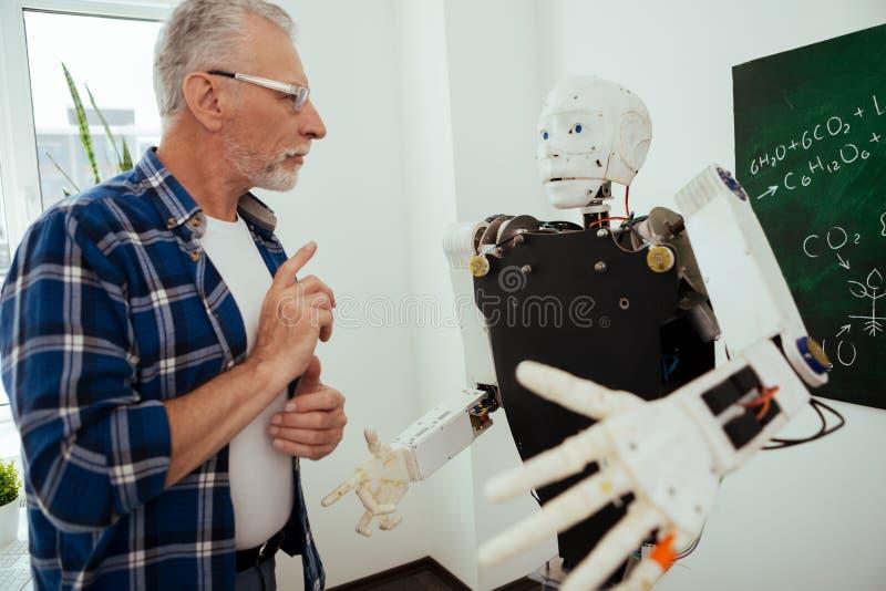 Σοβαρό ηλικίας άτομο που στέκεται μπροστά από το ρομπότ στοκ φωτογραφίες με δικαίωμα ελεύθερης χρήσης
