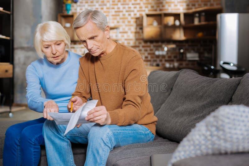 Σοβαρό ηλικίας ζεύγος που εξετάζει τους λογαριασμούς στοκ φωτογραφία με δικαίωμα ελεύθερης χρήσης