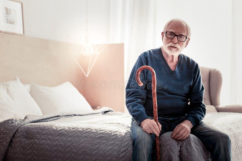 Σοβαρό ηλικιωμένο άτομο που κρατά ένα ραβδί περπατήματος στοκ φωτογραφία με δικαίωμα ελεύθερης χρήσης
