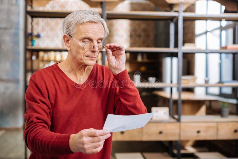 Σοβαρό ηλικιωμένο άτομο που κρατά τα γυαλιά του στοκ φωτογραφίες