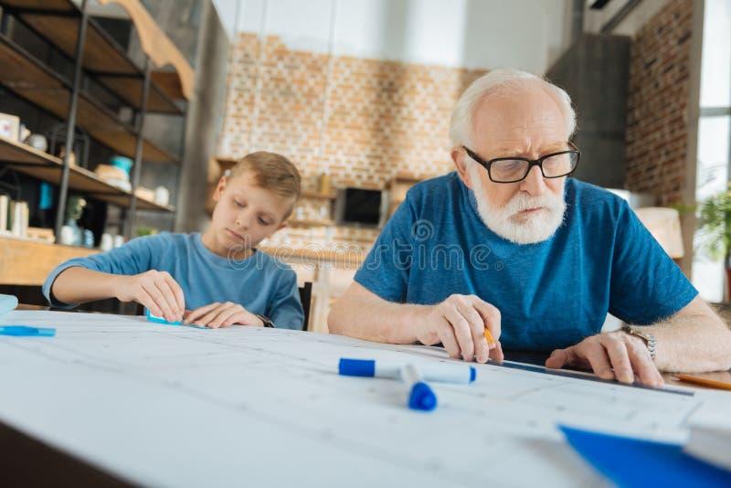 Σοβαρό ηλικιωμένο άτομο που περιλαμβάνεται στην εργασία στοκ εικόνες