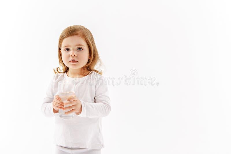 Σοβαρό θηλυκό παιδί που κρατά το γυαλί του aqua στοκ φωτογραφία