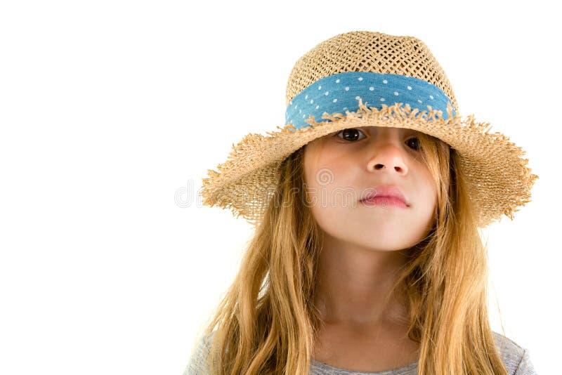 Σοβαρό μικρό κορίτσι που κοιτάζει αδιάκριτα έξω από κάτω από ένα καπέλο στοκ φωτογραφίες