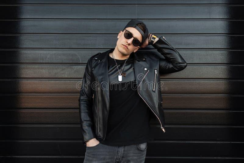 Σοβαρό νέο μοντέρνο άτομο hipster στα μοντέρνα μαύρα ενδύματα στα εκλεκτής ποιότητας γκρίζα τζιν σε μια ΚΑΠ στα γυαλιά ηλίου που  στοκ εικόνα με δικαίωμα ελεύθερης χρήσης