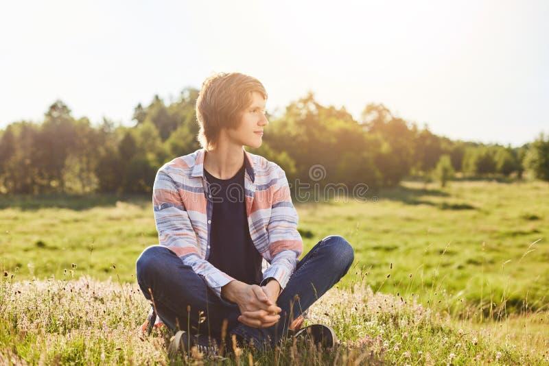 Σοβαρό στοχαστικό αγόρι στα περιστασιακά ενδύματα που κάθεται τα διασχισμένα πόδια στην πράσινη χλόη που κοιτάζει κατά μέρος με τ στοκ φωτογραφίες