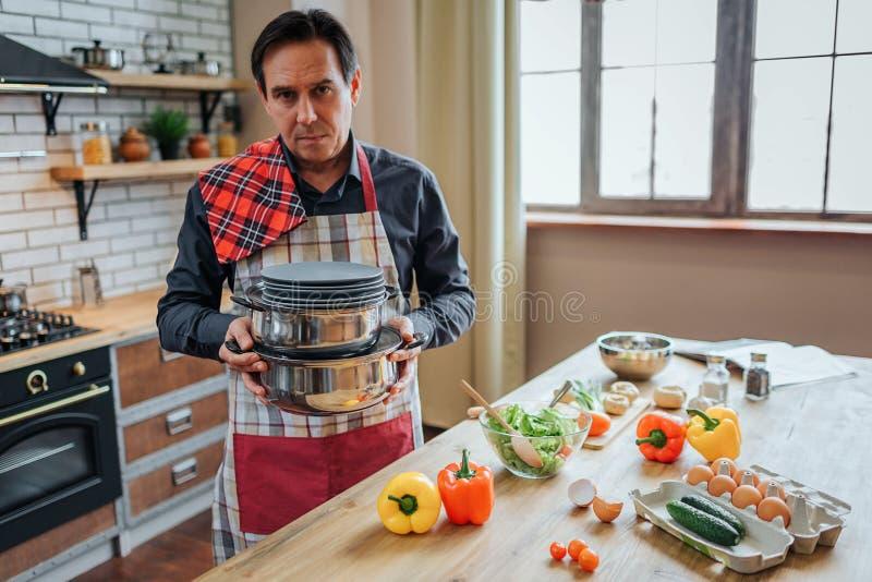 Σοβαρό συγκεντρωμένο άτομο στη στάση ποδιών μόνο στην κουζίνα Κρατά τα τηγάνια και τα πιάτα Στάση τύπων στον πίνακα Κοιτάζει δυστ στοκ εικόνες