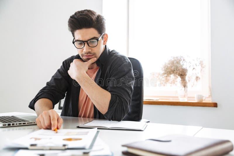 Σοβαρό όμορφο άτομο eyeglasses που λειτουργούν με τα έγγραφα στοκ φωτογραφία με δικαίωμα ελεύθερης χρήσης