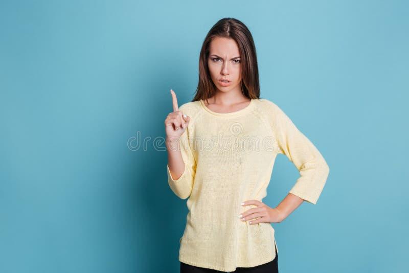 Σοβαρό όμορφο κορίτσι που δείχνει το δάχτυλο επάνω και που εξετάζει τη κάμερα στοκ φωτογραφία με δικαίωμα ελεύθερης χρήσης