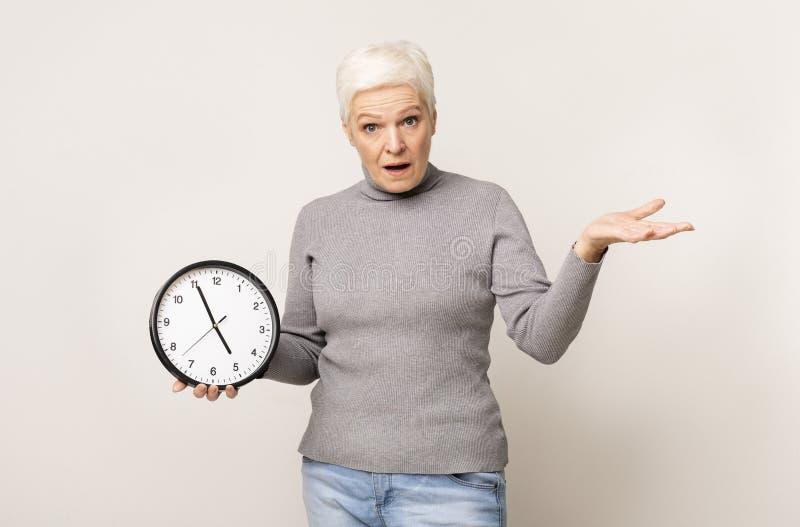 Σοκαρισμένη ηλικιωμένη γυναίκα που κρατά το ρολόι του τοίχου και κάνει χειρονομία στοκ εικόνες με δικαίωμα ελεύθερης χρήσης