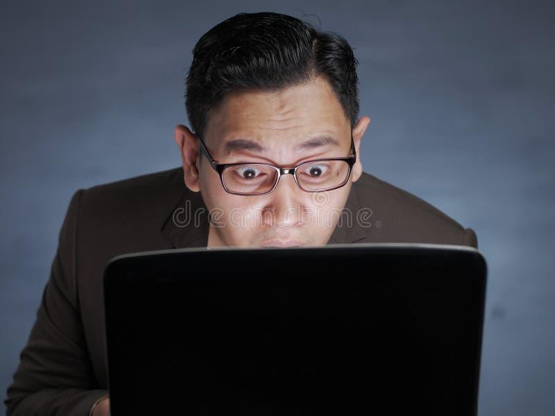 Σοκαρισμένος άνδρας που κοιτάζει το φορητό υπολογιστή στοκ εικόνες