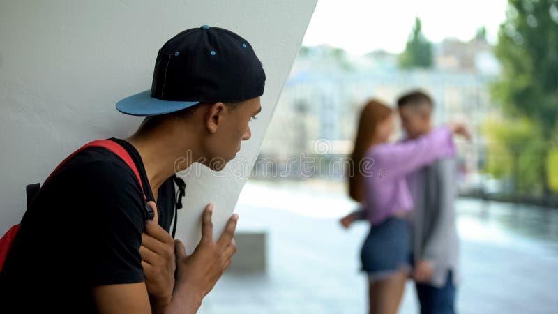 Σοκαρισμένος μαύρος έφηβος που ψάχνει κοπέλα να αγκαλιάζει συμμαθητή, ανεπανάληπτη αγάπη στοκ εικόνες με δικαίωμα ελεύθερης χρήσης