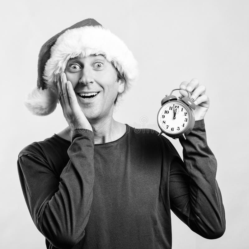 Σοκαρισμένος όμορφος άντρας με Santa hat Άντρας με ξυπνητήρι Είναι σχεδόν δώδεκα η ώρα Χριστούγεννα, πωλήσεις και εκπτώσεις στοκ εικόνες