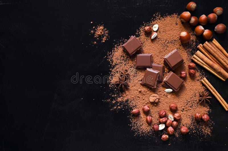 Σοκολάτα γάλακτος σε ένα σκοτεινό υπόβαθρο με τη σκόνη και τα καρύδια κακάου στοκ φωτογραφία