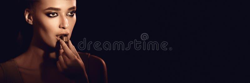 Σοκολάτα δαγκωμάτων Όμορφο κορίτσι στο σκοτεινό υπόβαθρο στούντιο στοκ εικόνα