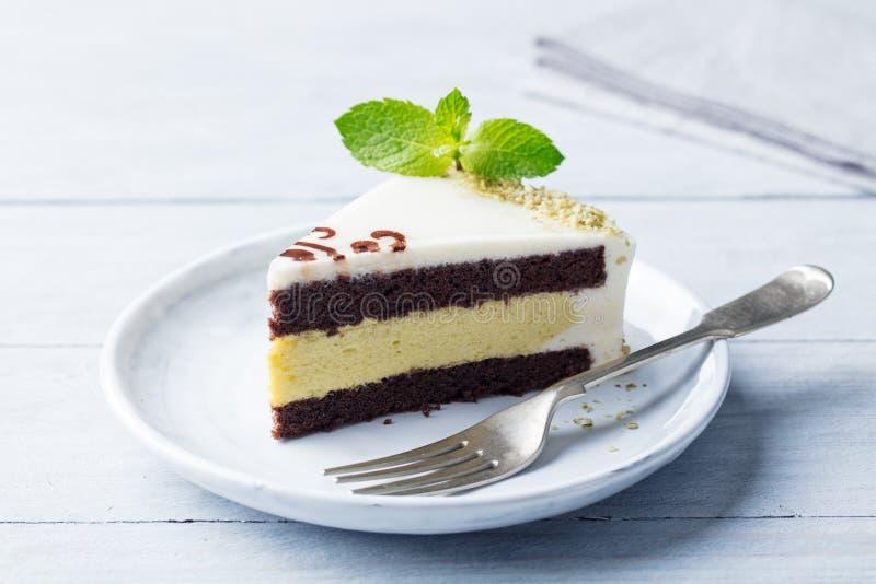 Σοκολάτα, κέικ φυστικιών με το φρέσκο φύλλο μεντών σε ένα πιάτο Ξύλινη ανασκόπηση στοκ εικόνα