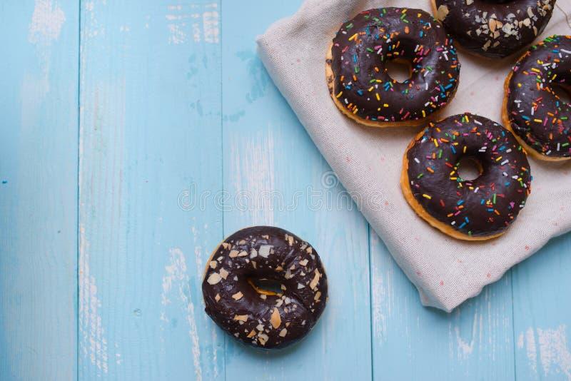 Σοκολάτα που βερνικώνεται donuts στο ξύλινο υπόβαθρο με το κενό διάστημα στοκ εικόνα