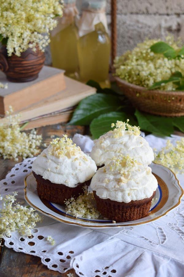 Σοκολάτα capcakes με την κρέμα βανίλιας που ψεκάζεται με τα άσπρα λουλούδια σοκολάτας και elderberry κόκκινος τρύγος ύφους κρίνων στοκ φωτογραφίες